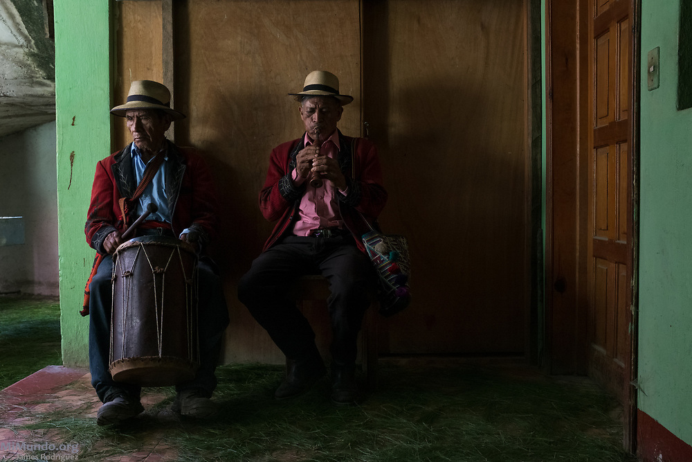 Ixil Mayan elders Nicolas Bernal Ramirez (left), 79, and Jacinto Raymundo Raymundo, 70, play the Cortez drum and Chirimía flute, respectively, as dozens of residents from Nebaj gather to receive the human remains of 36 war victims. Most of the victims, exhumed from mass graves in Xe'xuxcap, near Acul, starved in the mountainside while fleeing State-led repression in 1982. Most of the remains, exhumed by members of the Forensic Anthropology Foundation of Guatemala (FAFG) in 2013, were identified using DNA analysis and buried 35 years after their death. Acul, Nebaj, Quiché, Guatemala. February 2, 2017.