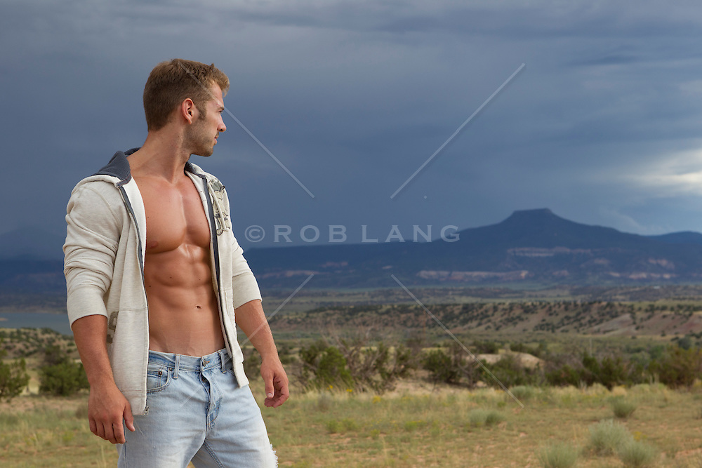 Good looking man with an open shirt standing in a field overlooking Abiquiu, New Mexico