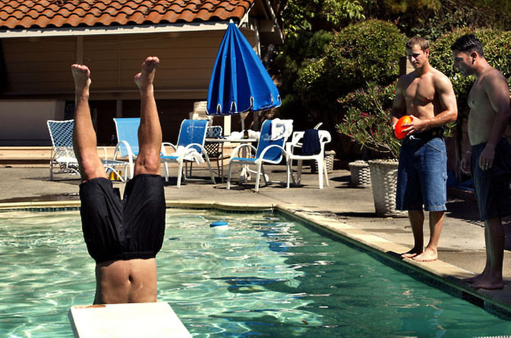 Frank Menechino, major league baseball player dives into the backyard swimming pool at the Lafayette home he shares with four other Oakland Athletics teammates including Mark Ellis (holding nurf football) and friend and former player F.P. Santangelo (far right).  They were playing a game and the person who could not catch the football had to dive into the pool.  Menechino lost.