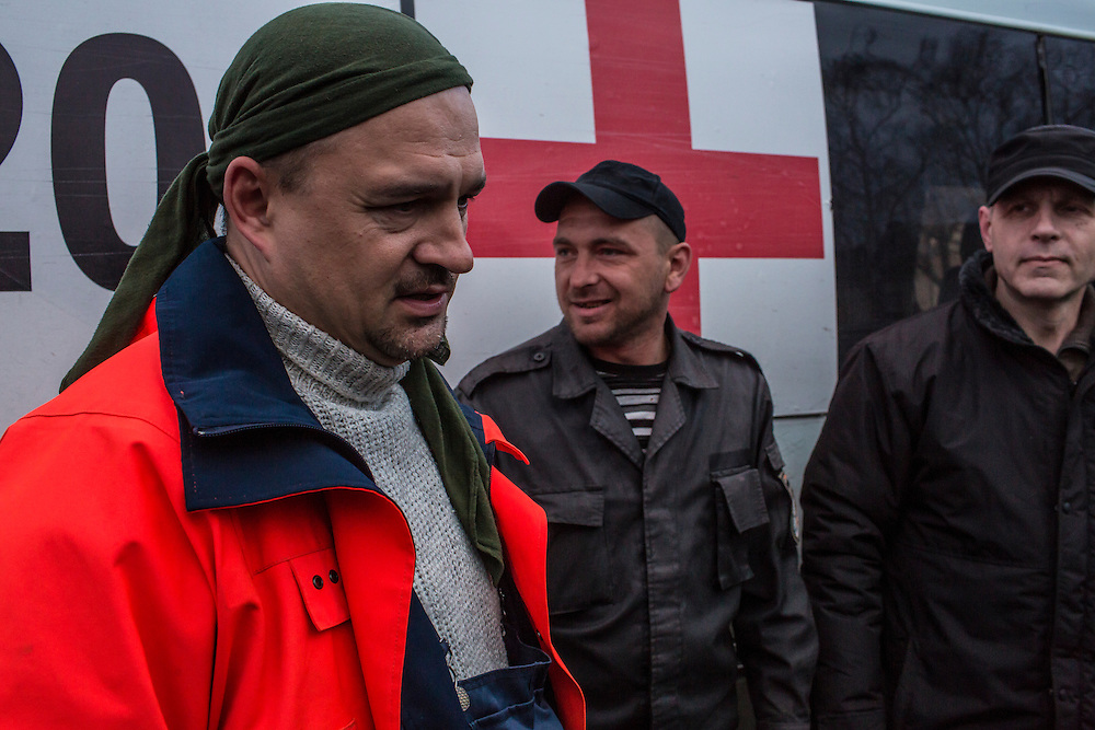 Igor Slyusar, age 40, from Kiev; Yevgeny Kishkin, age 31, from Kakhovka in the Kherson region; and Igor Slyusar, age 40, also from Kiev (from left), all members of the Black Tulips, stand outside the vehicle they use to collect unclaimed bodies on Wednesday, April 9, 2015 in Velyka Novosilka, Ukraine.