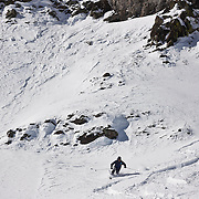 SHOT 3/12/10 11:46:00 AM - A skiier cuts fresh tracks through some powder in an open bowl at Silverton Mountain in Silverton, Co. Skiing and snowboarding at Silverton Mountain in Silverton, Co. Silverton Mountain is unique amongst ski resorts requiring a guide (most of the season), avalanche gear and limiting the number of daily visitors. There are multiple bowls, chutes, cliffs and natural terrain features to be discovered during a visit to Silverton Mountain. It is the highest Ski Area in North America with a peak of 13,487' and it is also the steepest with no easy way down. The mountain is left in it's natural state with the exception of the avalanche reduction work which occurs. There is only one chair at the mountain though most skiiers and snowboarders will end up hiking in various directions at the top. The mountain also features heliskiing trips for $159 a trip (at the time of visit). The mountain opened in 2002. (Photo by Marc Piscotty / © 2010)