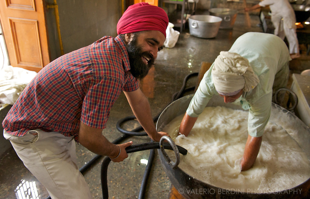 Two men enjoy washing tens of kilograms of rice with fresh water. Temperature in Amritsar in summer easily reaches 40 C