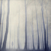 Abstraction of a man strolling through a foggy forest. Textured photography.<br />