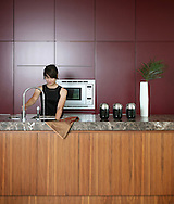 young attractive women washing up in kitchen sink with red kitchen units in background