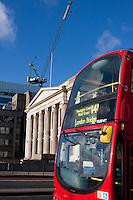 london bus passes fishmongers hall and construction crane