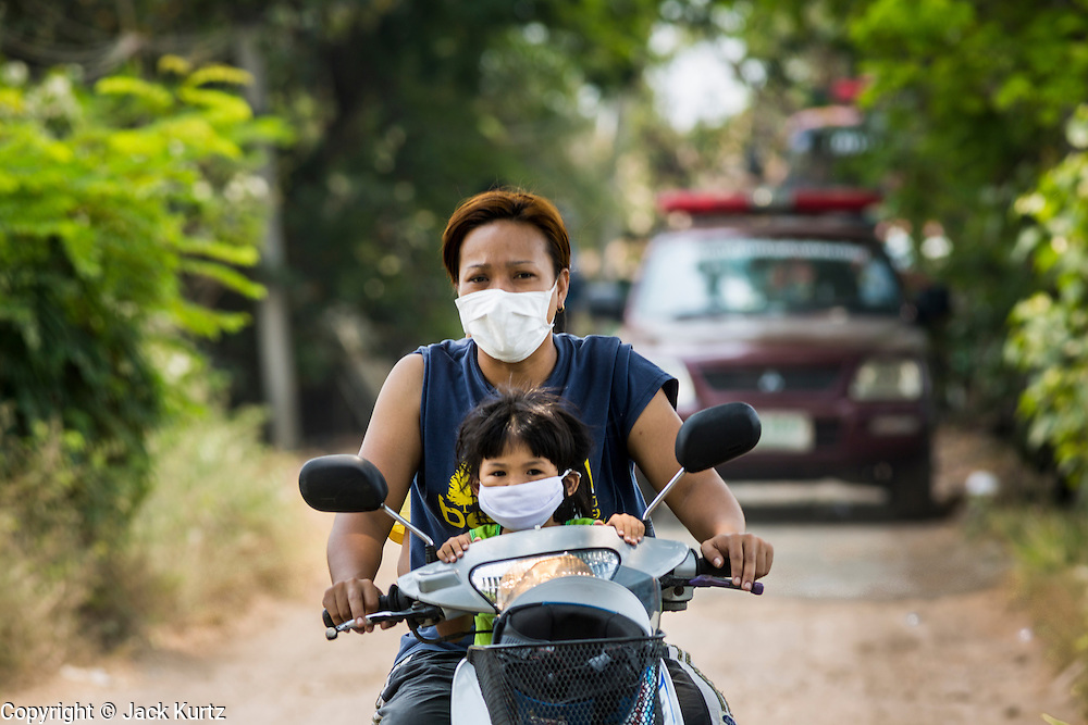 17 MARCH 2014 - PHRAEKSA, SAMUT PRAKAN, THAILAND:  Residents of a landfill wear breathing filters because of the smoke from a fire burning in the landfill. A fire apparently spontaneously started in the landfill in Samut Prakan over the weekend and threatens the homes of workers who live near the landfill. The fire Officials said the fire started when garbage in the landfill burst into flames and the flames were spread by hot, dry winds. Hundreds of people have been evacuated because of the fire and acrid smoke from the fire has spread as far as Bangkok. It hasn't rained in central Thailand in more than three months, impacting agriculture and domestic water use. Many farms are running short of irrigration water and salt water from the Gulf of Siam has come up the Chao Phraya River and infiltrated the water plants in Pathum Thani province that serve Bangkok.  PHOTO BY JACK KURTZ