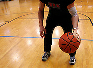 Bob Radocy of TRS Inc. bounces a basketball with a prosthetic hand designed for the sport at a gym in Boulder, Colorado August 21, 2009. Radocy designs and builds prosthetic attachments that allow amputee athletes to participate in multiple sports.  REUTERS/Rick Wilking (UNITED STATES)