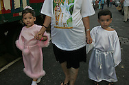 Dressed like angels only as they can be the children are led to the procession.