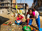 02 MARCH 2017 - SANKHU, NEPAL: Women do their laundry at a public tap in front of a storage depot for construction and rebuilding supplies in Sankhu. There is more construction and rebuilding going on in Sankhu, west of central Kathmandu, than in many other parts of the Kathmandu Valley nearly two years after the earthquake of 25 April 2015 that devastated Nepal. In some villages in the Kathmandu valley workers are working by hand to remove ruble and dig out destroyed buildings. About 9,000 people were killed and another 22,000 injured by the earthquake. The epicenter of the earthquake was east of the Gorka district.   PHOTO BY JACK KURTZ