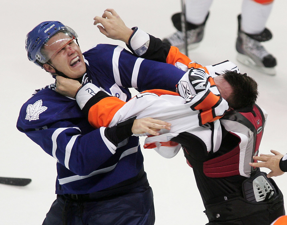 Luke Schenn of the Toronto Maple Leafs is hit by Zac Rinaldo of the Philadelphia Flyers in a second period fight during an exhibition game at the John Labatt Centre in London, Ontario, September 23, 2010.<br /> REUTERS/Geoff Robins (CANADA)