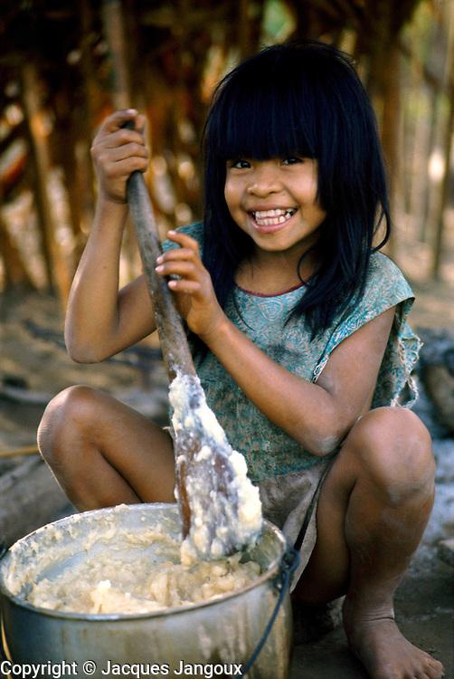 Shipibo Indian girl preparing food in village on shores of Ucayali River, Peru. Shipibo language belongs to the Panoan family.