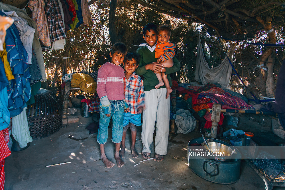 Four children smiling happily in their home made of hay that keeps the house ventilated in the hot summer months.