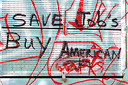 """Graffiti adorns the side of a railroad freight car, imploring everyone that sees it to """"Save Jobs Buy American""""."""