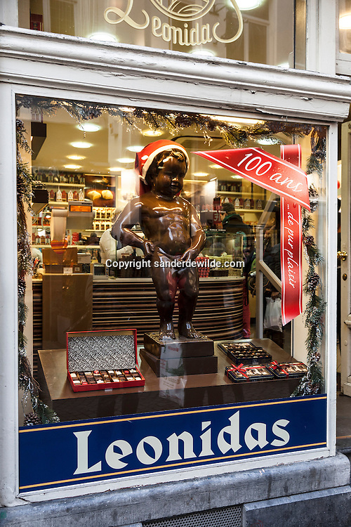 Brussels, Belgium, 2012 19 December. Belgian chocolate brand Leonidas starts celebrating its 100 years exitence in 2013. At the famous Belgian medieval statue Manneken Pis (peeing man) people gathered today. A big statue in chocolate in the window of a magazine wearing a christmas hat.