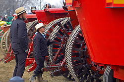 Young amish boy and father inspect farm equipment at Lancaster county spring mud sale auction.