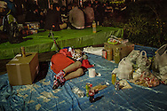 Young man passes out early at o-hanami, cherry blossom viewing, festival amidst the remains of the celebration.  Ueno Park, Tokyo, Japan.
