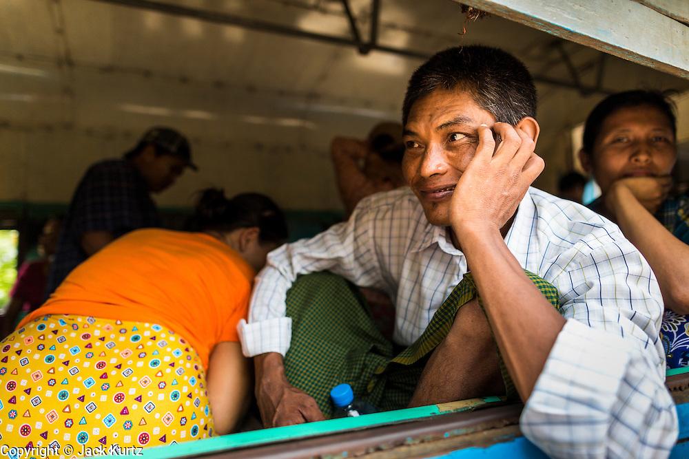05 JUNE 2014 - YANGON, YANGON REGION, MYANMAR: A man rides the Yangon Circular Train. The Yangon Circular Train is a commuter train that circles Yangon, Myanmar (Rangoon, Burma). The train is 45 kilometers long, makes 38 stops and takes about three hours to make a loop of the city.     PHOTO BY JACK KURTZ