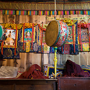 Drums hang from the ceiling at Tsamkhang Monastery (which practices Tibetan Buddhist religion), in Khunde village (12,600 feet / 3840 meters), in Sagarmatha National Park, in the Himalaya of eastern Nepal. Sagarmatha National Park was created in 1976 and honored as a UNESCO World Heritage Site in 1979.
