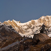 Annapurna I (on the right; 26,545 feet / 8091 meters elevation) is the world's 10th highest peak. The lower jagged peak at center left is Fang (or Baraha Shikhar 25,088 feet / 7647 meters). On the left, the full moon sets over Annapurna South (also known as Annapurna Dakshin, or Moditse; 23,684 feet / 7219 meters), which is shorter and closer than both other peaks, but looks taller from this perspective. This dawn view is from Annapurna South Base Camp (ABC; at 13,550 feet elevation) in the Annapurna Range of Nepal. Tibetan Buddhist prayer flags fly from a monument which honors fallen climbers. (Panorama stitched from 4 images.)