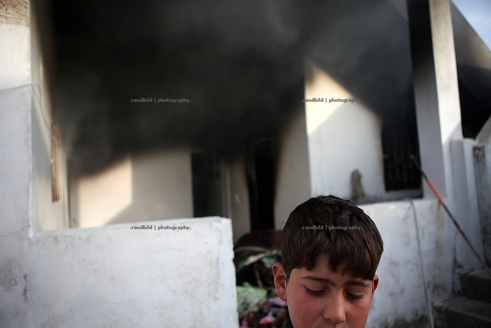 A boy in front of his familiys house which still burn after it was set on fire by syrian troops. On 22. February the syrian army attacked the village of Kureen, Province of Idlib, Syria. Kureen was among the first villages in the northwest of Syria controlled by the opposition. Some villagers and members of the defence units escaped to surrounding olive orchards, when the attack begun in the early morning. A majority of the inhabitants didn´t manage to escape. The heavy shelling lasts 7 houres. Soldiers searched all houses, burnt some of them down, loote shops, stole cars and furniture. About 60 motorcycles were burnt down. Tanks demolished several houses. 6 men were executed. One woman died as a result of an heart attack.