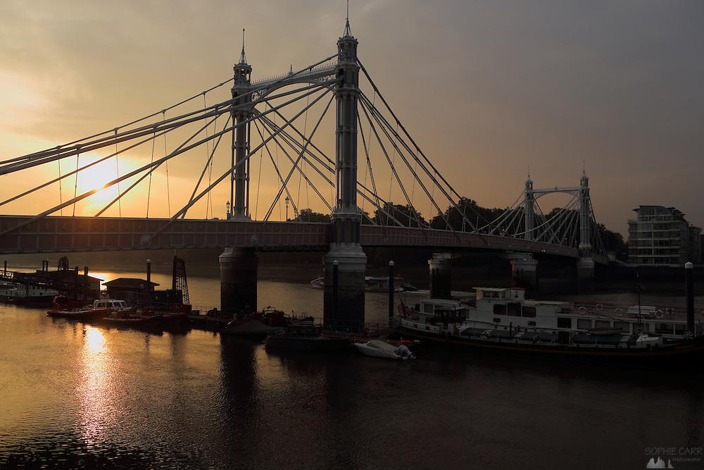 Albert Bridge in London seen at sunrise from Chelsea Embankment