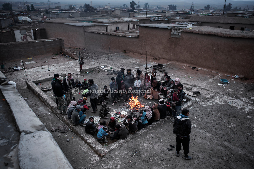 Iraq: Refugees who fled west Mosul warm themselves at in Kaysumah village from where, the day after, Iraqi army vehicles will take them to IDP camps. Alessio Romenzi