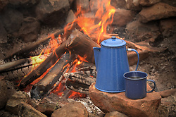 Enamel coffe pot percolator and blue enamel coffee cup resting on a rock near a campfire