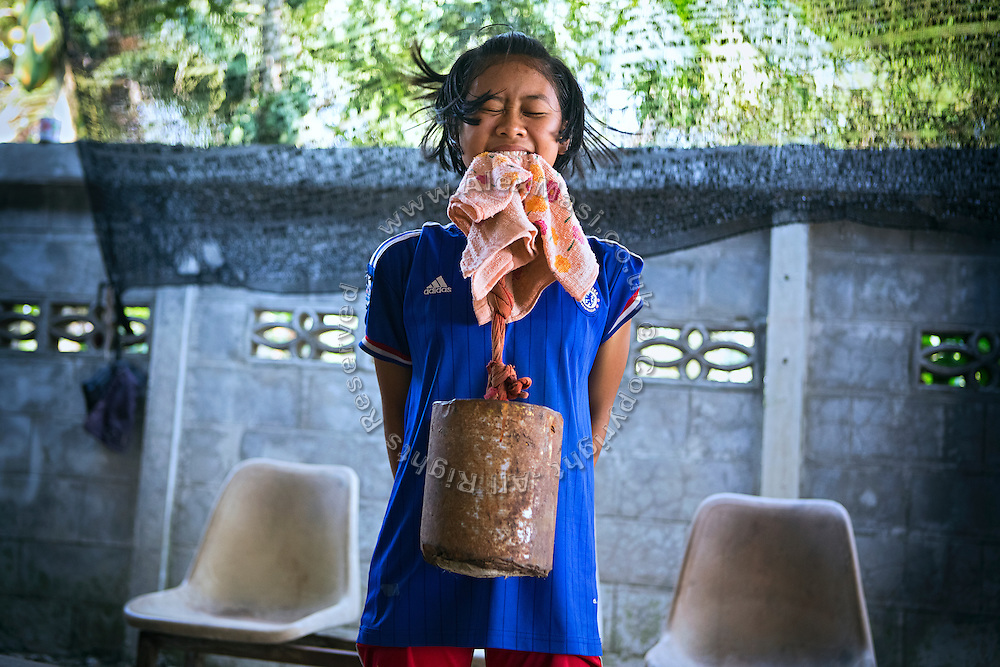 Phatsorn Bunmasen, 14, is lifting a weight using her neck and mouth while training at the gym where she practises Muay Thai boxing, in a village near Ubon Ratchathani, northeast Thailand.