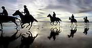 A group of riders enjoy a nice gallop at sunset along the Oregon Coast near Manzanita.