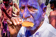 Indian man is eating popsicle during of Holi festival in the streets of Hampi, Karnataka, India, on  March 5, 2015. Holi, also known as the Festival of Colors, heralds the beginning of spring and is celebrated all over India.<br /> Photo by Oren Nahshon