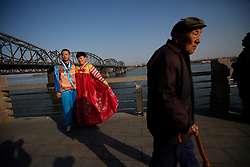 An elderly man walks past Chinese tourists dressed in Korean traditional costumes posing for photos by the Yalu River Bridge where across is the North Korean town of Sinuiju in Dandong, Liaoning Province, China on 07 April 2013. China on 07 April said its embassy in Pyongyang was still 'operating normally' following North Korea's warning to diplomats that it could only guarantee their safety until Wednesday. Beijing had asked North Korea to protect the safety and interests of Chinese citizens and businesses in the country.