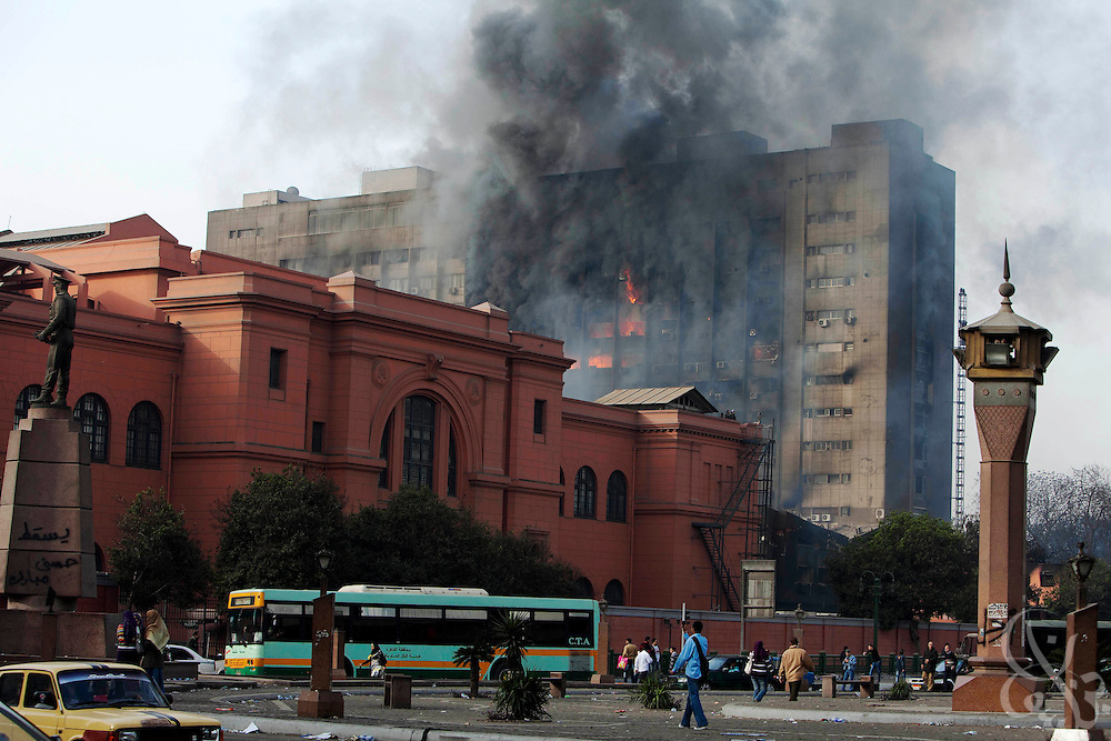 A government council building burns behind the Egyptian museum following another night of unrest January 29, 2011 in Cairo, Egypt. Massive and unprecedented protests across Egypt are threatening to bring the nearly 30 year reign pf President Honi Mubarak to an end.
