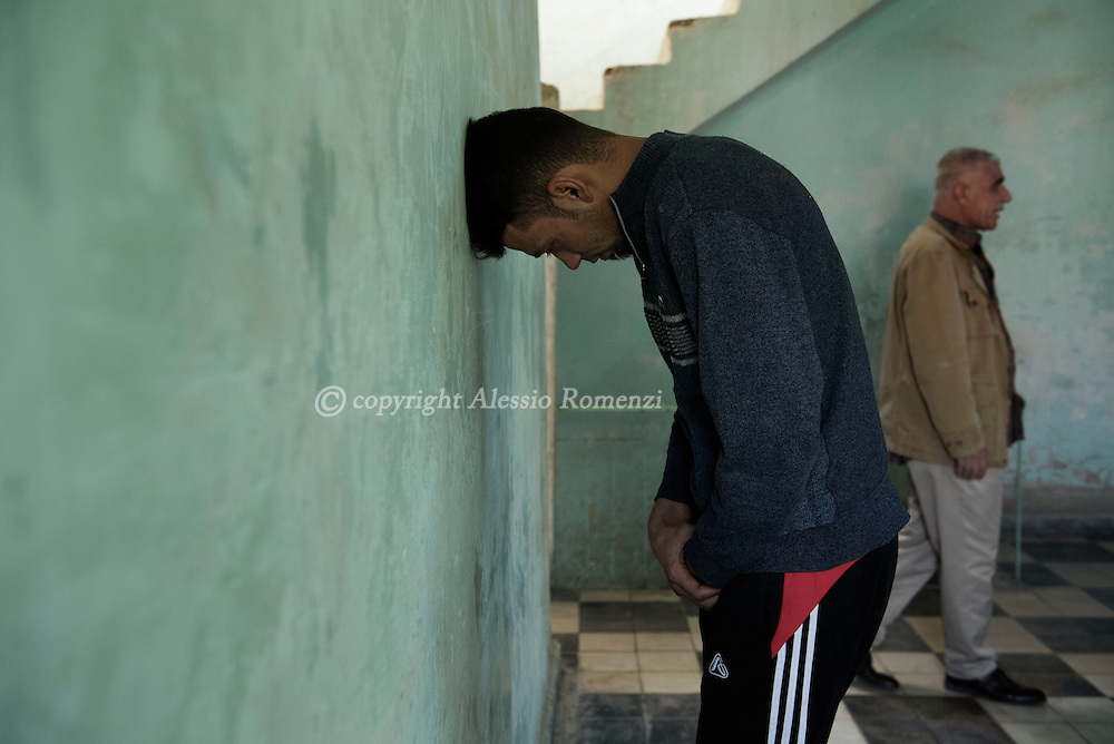 Iraq, Kirkuk: Addi Abbas Sabbhan 24yo, accused of being an ISIS member, stands facing the wall inside one of the facilities of the prison in Kirkuk. Alessio Romenzi