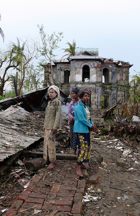 Women standing next to the roof of the monastery that had collapsed during Cyclone Nargis. Around two hundred villagers who were taking refuge in the temple died when it collapsed.