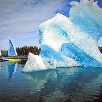 Catmaran Sailboats exploring the frigid waters of Prince William Sound with a large ice floe in the foreground