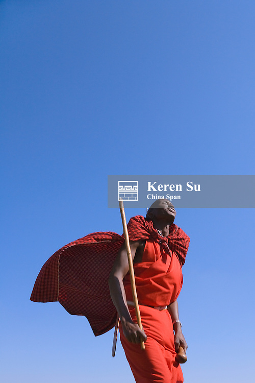 Masai tribesman performing jumping dance with spear, Masai Mara, Kenya