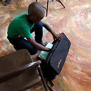 A young student packs up his instrument at the end of the day.