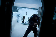 A coast guard opens the door in the early hours of the morning to have a better view of any boats trying to make it to Greece from Turkey.   Image © Angelos Giotopoulos/Falcon Photo Agency..