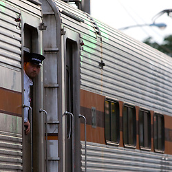 The conductor of a Chicago South Shore and South Bend commuter train leans out to check that everyone has boarded before proceeding to Chicago.