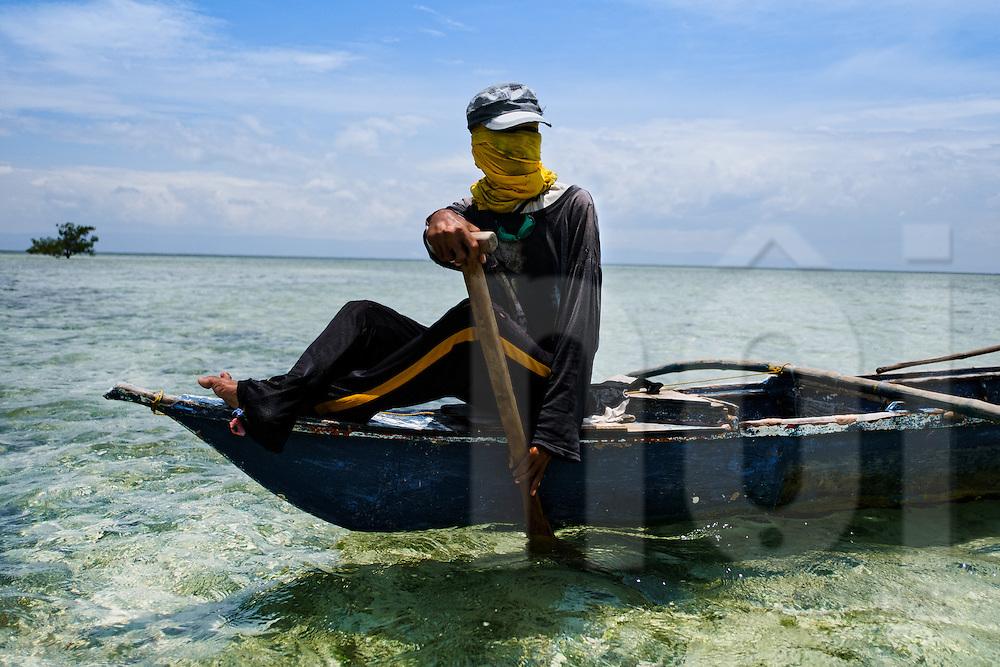 A filipino fisherman rows along Panglao Reef Flat, Central Visayas,  Philippines, Southeast Asia