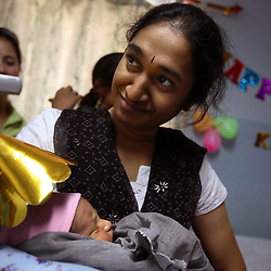 A still-unnamed newborn is held by his biological mother during a birthday party held for him on his last day at the clinic before going home in Anand, India on April 12, 2007. (The party was also meant to celebrate the first birthday of the first surrogate baby at the clinic). The biological parents of the newborn, who wished not to be named, are from Hyderabad in southern India and had been trying for a baby for 15 years and suffered six miscarriages. The surrogate Daxa (no surname), 28, agreed to be a surrogate so she could build a better house for her family. Dr. Patel currently has more than 25 women who have been implanted with embryos at her clinic. A few have already gone through the process once and are eager for a second go-round. While Patel claims many of the women do this for altruistic reasons, she acknowledges that money was the primary reason these women had queued up to be surrogates; without it, the list would be short, if not nonexistent. Payment usually ranges from about $2,800 to $5,600, a fortune in a country where annual per capita income hovers around $500.