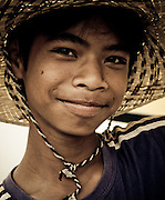 A teen-aged boy wearing a straw hat makes his business selling bread and cheese to tourists in Siem Reap, Cambodia, Southeast Asia.