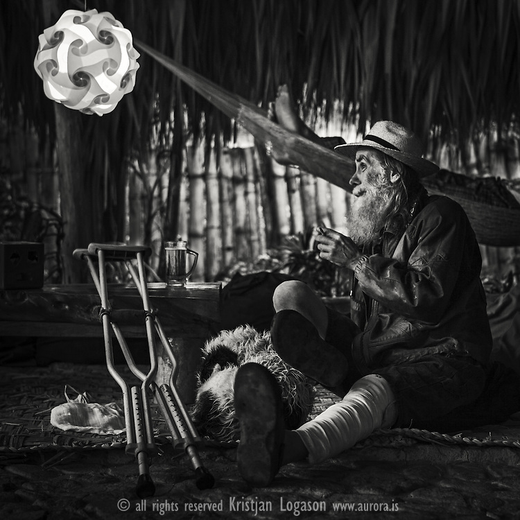 Man with hat and beard having a cigarette and beer while resting his hurt leg inside cafe ZooLa in San Pedro by Lake Atitlan in Guatemala