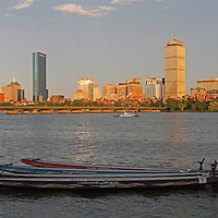 Photo of Boston Dragon Boats with the Boston Back Bay skyline showing historic and modern architectural landmarks such as The Prudential Center, John Hancock tower and the Boston Sheraton Hotel on a beautiful afternoon.<br />