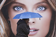 Israeli woman passes by a make up advertising sign while smoking a cigarette after rain started pouring down in Jaffa st` in the center of Jerusalem, on November 21 2011. Photo by Oren Nahshon.