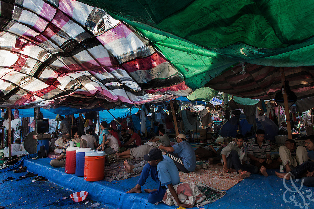 Supporters of deposed President Mohamed Morsi try to escape the unrelenting afternoon sun under makeshift tarped tent structures at the Rabaah al-Adawiya protest camp Monday, August 12, 2013 in the Nasr City District of Cairo, Egypt. Morsi supporters and other groups opposed to the military coup in Egypt have been occupying the camp for more than a month and say they are determined to remain as long as it takes to restore the ex-president to power.