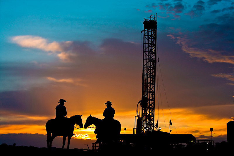 Stock photo of two cowboys on horseback in front of an oil and gas drilling rig at sunset in Texas