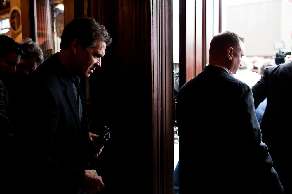 Republican presidential candidate Rick Perry, left, leaves after speaking to supporters at Kuhly's Bar & Grill on Thursday, December 22, 2011 in Ottumwa, IA.
