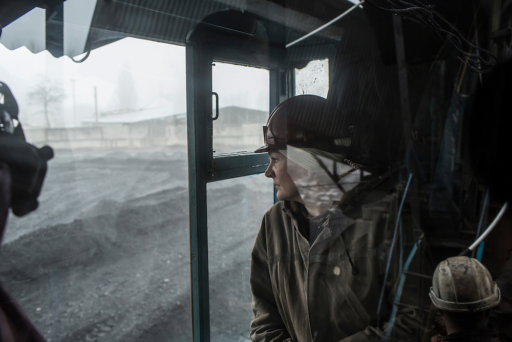 A woman watches as coal is dumped from a conveyor for storage before being loaded onto trains at the Shcheglovskaya Coal Mine on Friday, March 25, 2016 in Makiivka, Ukraine.
