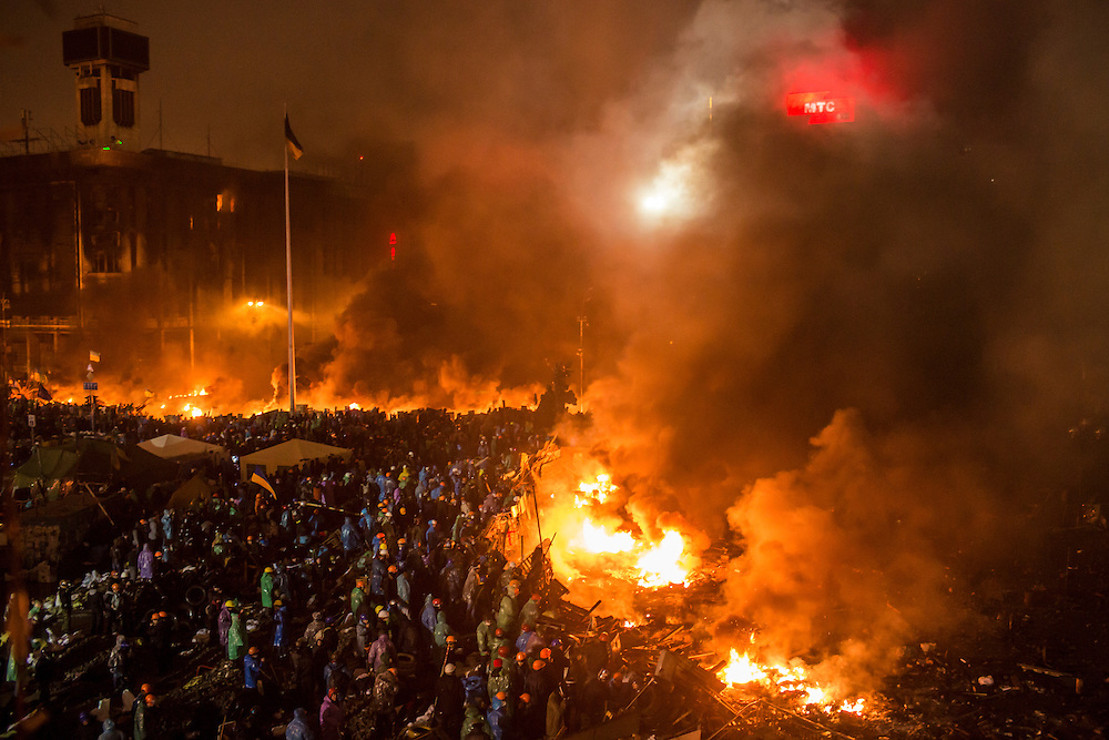 KIEV, UKRAINE - FEBRUARY 19: Anti-government protesters stand behind a line of burning tires and debris on Independence Square on February 19, 2014 in Kiev, Ukraine. After several weeks of calm, violence has again flared between anti-government protesters and police as the Ukrainian parliament is meant to take up the question of whether to revert to the country's 2004 constitution. (Photo by Brendan Hoffman/Getty Images)